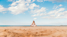 Senior Woman In Lotus Pose Sitting On The Sand - Yoga At Beach - Calm And Meditation Concept