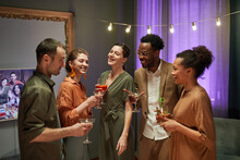 Waist Up Portrait Of Diverse Group Of Friends Laughing And Chatting While Enjoying Party At Home