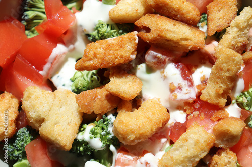 Photo Closeup of fresh salad with green broccoli, red tomatos, toasted croutons, and w