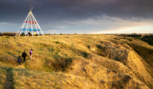 Medicine Hat Alberta Canada, May 13 2021: A Family Walks Outdoors Along A Hiking Trail In Seven Persons Coulee By The Sammis Tepee At Sunset.