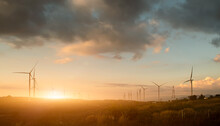 Silhouette Of Wind Turbines At Sunset.