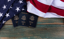 US Flag With USA Passport Books On Vintage Wooden Planks For Travel Concept