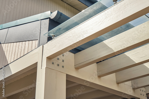 Photo Carcass of comfortable pergola made with plain wooden beams with glass roof at m