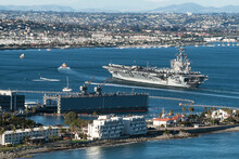 An Aircraft Carrier Being Led By A Tugboat Into San Diego Bay In California With A Naval Base In The Foreground And The City Of San Diego In The Background