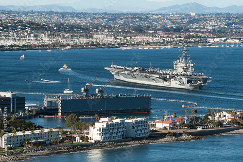 Obraz na płótnie an aircraft carrier being led by a tugboat into San Diego Bay in California with