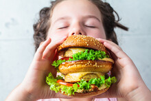 The Child Is Eating Big Vegan Burger, Close-up.