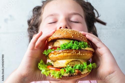 The child is eating big vegan burger, close-up. Fototapeta