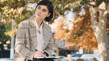 Young Businesswoman Looking Thoughtful Sitting On Street And Wor