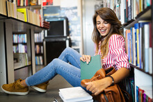 Education, High School, University, Learning Concept. Smiling Student Girl Reading Book At Library
