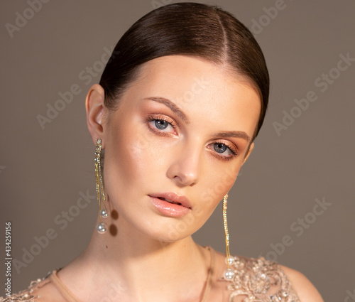 Portrait of an elegant woman. The hair is slicked back smoothly. In the ears are gold earrings with beads. Clean skin. Beige color. Look straight ahead.