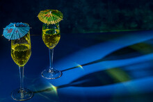 Two Flute Glasses With Sparkling Yellow Liquid With Colored Paper Umbrellas On Top, Cast Reflections And Shadows On A Blue Surface