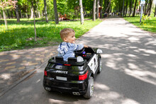 Back View Of Cute Little Caucasain Blond Toddler Boy Enjoy Having Fun Riding Electric Powered Police Toy Car By Asphalt Path Road City Park At Summer Day. Happy Child Playing Rc Vehicle Outdoors