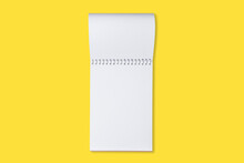 Schoo Or Office Notebook On A Yellow Background. Mock Up Of Spiral Notepad On A Table