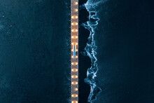 Aerial View Of Vehicle Driving On Illuminated Bridge Over The Frozen Lake In Trakai, Lithuania.