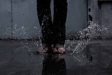 Low Section Of Man Standing In Water