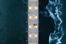 Aerial View Of Illuminated Wooden Pedestrian Bridge Over The Frozen Lake At Dusk In Trakai, Lithuania.