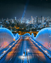 Aerial View Of Two People Standing On A Modern Bridge With Dubai Skyline In Background At Night, Dubai, United Arab Emirates-.