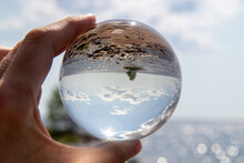 Close-up Of Hand Holding Glass Of Crystal Ball
