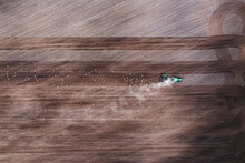 Aerial Top Down View Of Tractor Harrowing Agricultural Soil Land In Countryside, Kaunas, Lithuania.