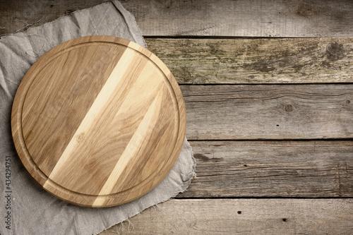 Billede på lærred empty round wooden cutting kitchen board on wooden background, pizza board, top