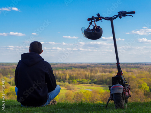 Carta da parati A young man on an electric scooter , modern transport