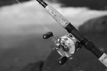 Close-up Of Fishing Reel Against Sea
