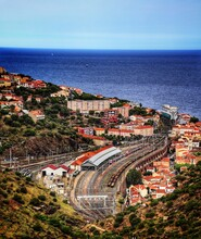 High Angle View Of Townscape And Railway By Sea Against Sky