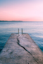 View Over The Sea During Sunset On A Dock With A Crack Leading The Viewers Eye Into The Water.