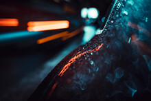 Droplets Over Hybrid Car With Light Trails. Winter Rainfall In A Dark Night With City Lights