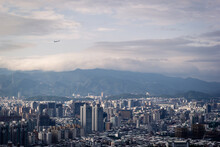 Cityscape Of Taipei With Mountain Background And Plane In The Sky