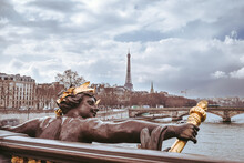 Sculture In A Bridge Crossing Paris City, With The Eiffel Tower In The Background.