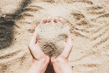 Close-up Of Hand Holding Heart Shape On Sand