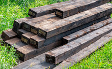 New Railway Sleepers Impregnated With Cryosote Lie On Green Grass Stacked On Top Of Each Other.