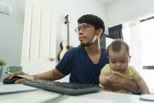 Asian Father Working From Home And Taking Care His Little Baby Son. Designer Male Using Computer During Quarantine