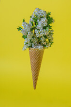 Ice Cream Cone With Flowers On A Yellow Background. The Concept Of Minimal Food.