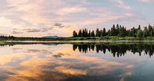 A Panoramic Photograph Of A Gorgeous Sunrise With An Explosion Of Clouds And Colors Reflect Off The Waters Of The Snake River In The Oxbow Bend Area Of Grand Teton National Park, Wyoming, USA.