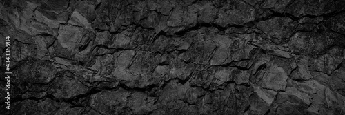 Volumetric rock texture with cracks. Black stone background with copy space for design. Wide banner.