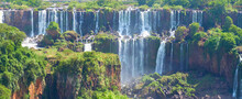 Iguazu Waterfalls In Argentina, View From Devil's Mouth. Panoramic View Of Many Majestic Powerful Water Cascades With Mist And Splashes. Panoramic Image Of Iguazu Valley With Lush Subtropical Forest.