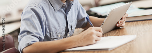 Fotografia A boy sitting at a desk using a digital tablet.