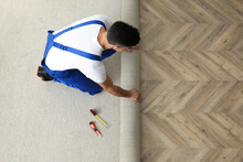 Worker Rolling Out New Carpet Indoors, Above View