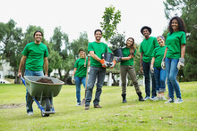 Group Of Happy Environmentalists With Potted Plants And Wheelbarrow In Park