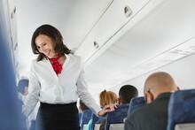 Flight Attendant Talking To Passengers In Airplane