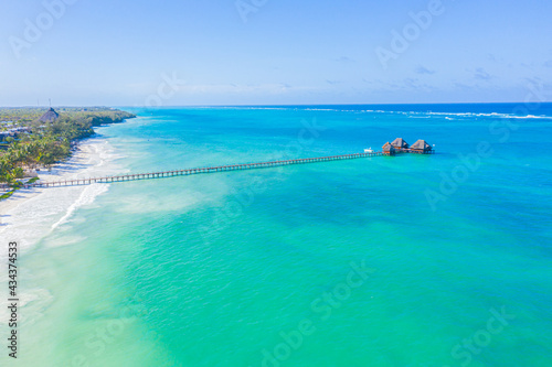 Aerial shot of the Stilt hut with palm thatch roof washed with turquoise Indian ocean waves on the white sand sandbank beach on Zanzibar island, Tanzania Fototapet