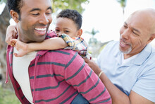 Little Boy Enjoying Piggyback Ride With Father And Grandfather