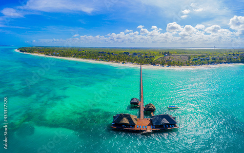 Canvastavla Aerial shot of the Stilt hut with palm thatch roof washed with turquoise Indian ocean waves on the white sand sandbank beach on Zanzibar island, Tanzania