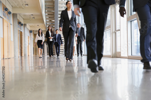 Canvas Group of business people walking in office building