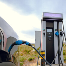 EV Car Plugged In Charger And EV Charger Station