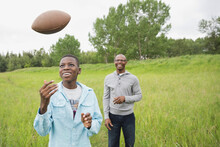 Father And Son Playing American Football Outdoors