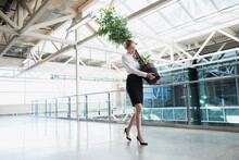 Businesswoman Carrying Potted Plant In Atrium