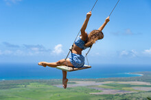Young Beautiful Caucasian Woman On The Rope Swing With Sea And Sky Background. Concept Of Dream And Happiness